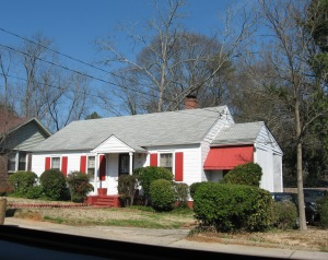 How cute is this house?!  I love the red awning and shutters.