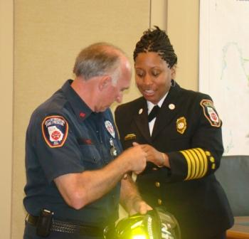 "Captain Pettit is congratulated by Chief Toni Dixon. Notice the helmet ""aglow""!"