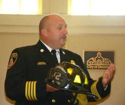 Asst Chief Tim Hatcher gets ready to present the Friefighters with their helmets.
